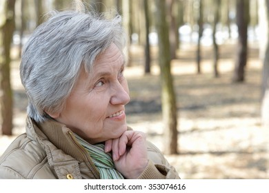 Pensive elder woman walking in the forest in autumn