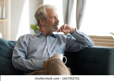 Pensive elderly 60s man sit relax on couch in living room drinking tea look in window distance thinking, thoughtful mature 50s husband rest on sofa at home feel sad pondering considering future