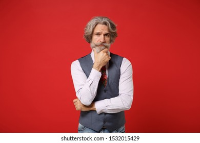 Pensive elderly gray-haired mustache bearded man in classic shirt vest colorful tie isolated on red background, studio portrait. People lifestyle concept. Mock up copy space. Put hand prop up on chin