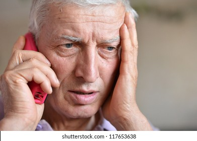 pensive elderly man calling on the phone