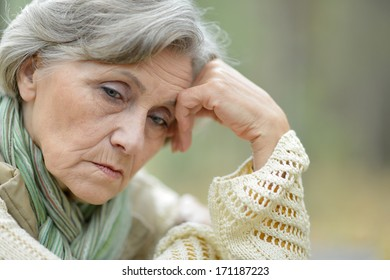 Pensive elderly woman on the background of autumn leaves