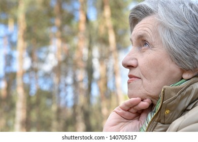 Pensive elderly woman walking in the forest in autumn