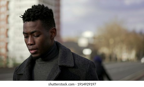 Pensive elegant black African man walking outside in city thinking about life