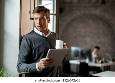 Pensive entrepreneur drinking coffee and using touchpad while standing in the office and looking away.