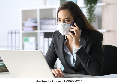 Pensive executive woman calling on smart phone avoiding coronavirus with mask sitting at the office