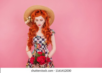 Pensive face. Summer sale concept. Beautiful stylish outfit. Pensive redhead model with hairstyle in hat on pink background. Fascinating girl in bright outfit. Beauty redhead woman with rose flowers