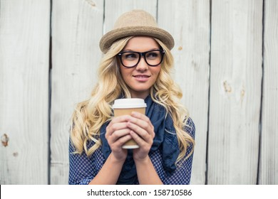 Pensive fashionable blonde holding coffee outdoors on wooden background