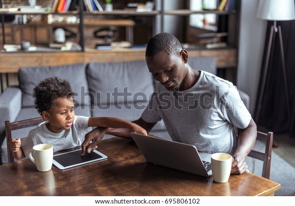 pensive father and son using laptop and tablet at home