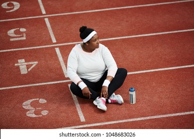 Pensive female in activewear sitting on one of stadium race tracks after training