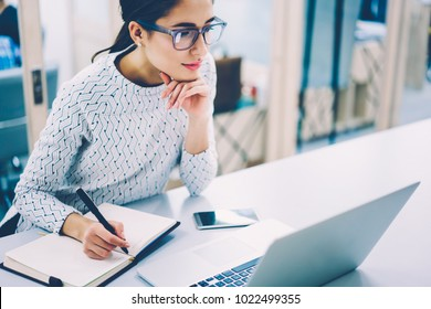Pensive female administrative assistant checking report on laptop reading information and noting data,skilled woman watching online video online pondering on creating publication writing in notepad