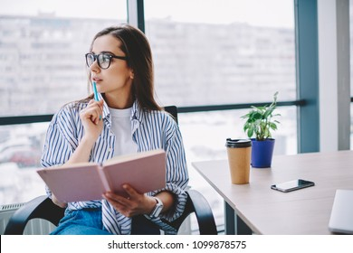 Pensive female author in eyewear looking away concentrated on idea for article sitting at desktop,skilled professional woman journalist pondering on publication holding pen and notebook in office