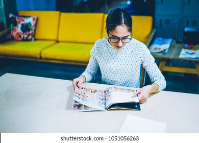 Pensive female editor of magazine reading issue for checking articles and publication while sitting at table ,concentrated woman choosing items in paper catalogue for buying furniture in office