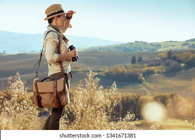 pensive fit woman hiker in hiking gear with bag with binoculars looking into the distance. summer hiking in Tuscany ,Italy.