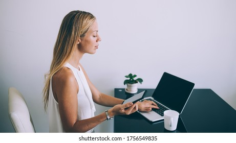 pensive focused female in formal clothes using netbook and smartphone while sitting at table with mug of tasty beverage and working on project against white wall in light contemporary office