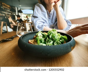 Pensive french woman talking in restaurant delicious green gourmand organic salad