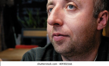 Pensive friendly man emotional close portrait with big expressive eyes significant nose and small stubble beard. Friendly silent reflection thoughtful scene.