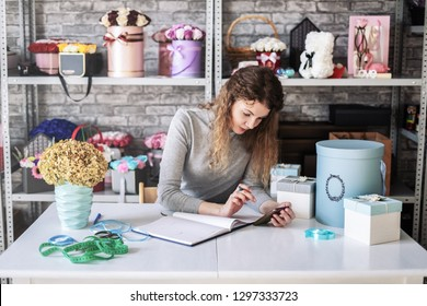 Pensive girl florist takes notes in a notebook in her flower shop. Around the gray background and a lot of bright bouquets of flowers.