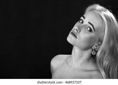 pensive girl with freckles and bare shoulders looking at camera on black background with copyspace, monochrome