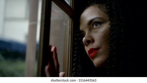 pensive  girl get nostalgic viewing in window standing inside house