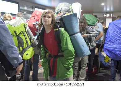 Pensive girl in a green windbreaker with a large backpack in the crowd at the station. She is going on a hike