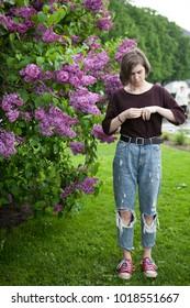Pensive girl posing in lilac bushes in the park