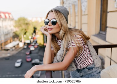 Pensive girl with shiny golden hair looking in distance with smile, standing on balcony. Portrait of romantic young lady in sunglasses chilling on terrace and enjoying city views.