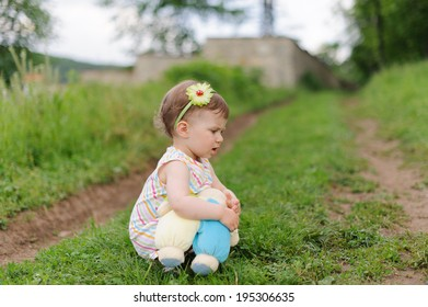 pensive girl sitting on path with toy