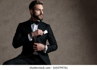 Pensive groom looking away with hope while wearing tuxedo and sitting on a stool on wallpaper studio background