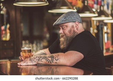 Pensive guy drinking light ale in pub