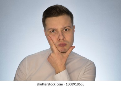 Pensive guy on a white background. Beautiful portrait of a guy. Portrait of a man on a white background