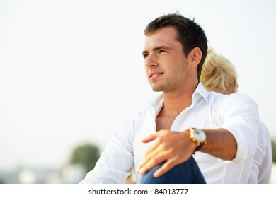 Pensive handsome man looking aside outdoors with his girlfriend sitting behind