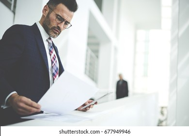 Pensive handsome matured male owner of corporation reading financial documentation standing near copy space for advertising, confident businessman in trendy formal wear checking accounting report
