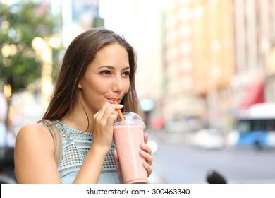Pensive happy woman sipping a milkshake in the street