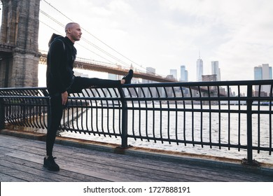 Pensive healthy ethnic male wearing black sports clothes and sneakers warming up before running on embankment railing on sunny urban background