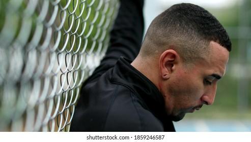 Pensive hispanic man leaning on metal fence thinking.