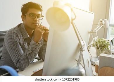 Pensive Indian It specialist checking information on computer screen