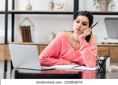 pensive indian woman with bindi studying with laptop at home