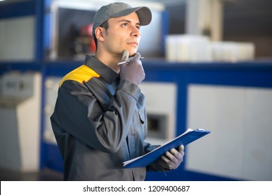 Pensive industrial worker holding a document
