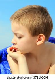 Pensive Kid on the Beach under Blanket