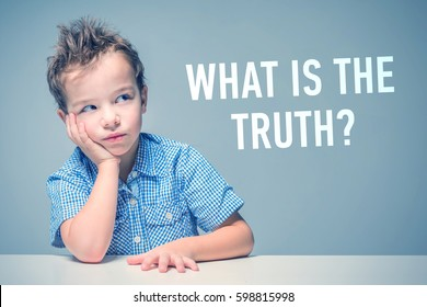 Pensive little boy in a blue shirt sitting at the table next to the inscription 'What is the truth?'