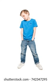 pensive little boy standing with hands in pockets and looking down isolated on white