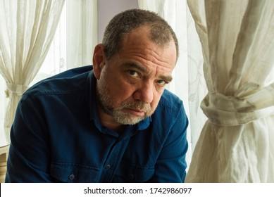 Pensive lonely man at home by the window