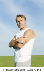 pensive looking man wearing a white tank top and grey shorts.