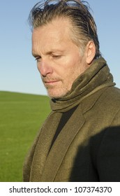 A pensive looking mature man with beard wearing scarf