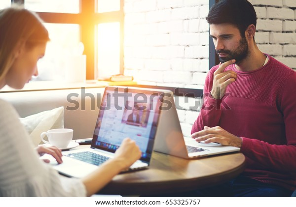 Pensive male bearded student with hipster girl spending free time on browsing internet websites on modern digital laptop computer with mock up area for your advertising text message in coworking space
