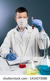 Pensive male doctor is observing blood sample in laboratory. Hi is sitting and writing