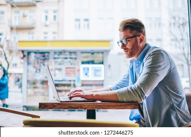 Pensive male graphic designer working on freelance at modern computer using wireless internet in cafe.Concentrated young man in eyewear keyboarding information on digital netbook during distance job