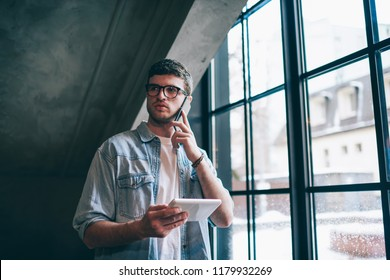 Pensive male user in spectacles for provide eyes protection pondering on telephone conversation indoors, concentrated hipster guy holding touch pad and calling to customer service via cellphone
