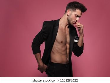 pensive man with bare chest looks down to side while wearing an undone black tuxedo and standing on red background