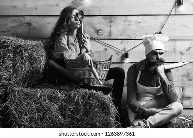 Pensive man chef cook or baker with beard and moustache in hat toque and cute girl cookee teenager in apron sit on straw bales on rustic background.